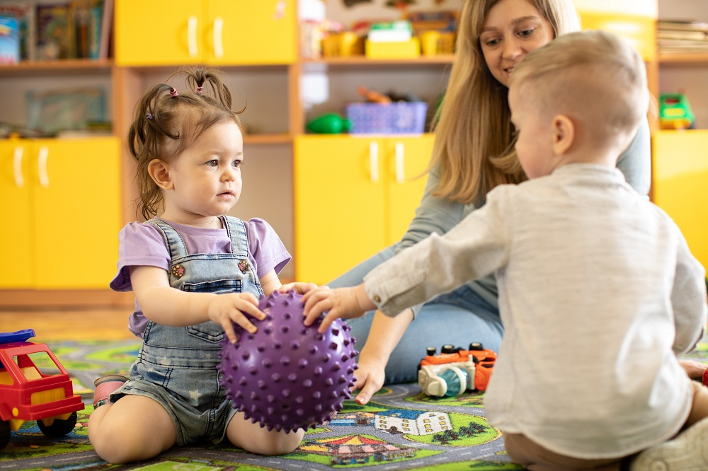 Boy and Girl Toddler Sharing a Purple Ball with Teacher Sitting with Them