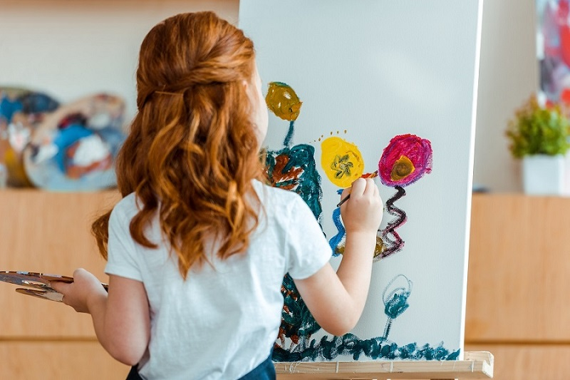 Preschooler in Spring Hill, TN painting on easel